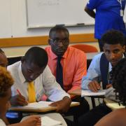 A group of students takes notes during the boys2MEN summit