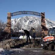 CU Boulder facilities management workers clear snow and ice from the steps to Farrand Field