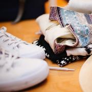 white sneakers, folded shirts and straw fedora hat on table