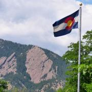 The majestic Flatirons provides a backdrop to the Colorado State Flag at the University of Colorado Boulder. (Photo by Casey A. Cass/University of Colorado)