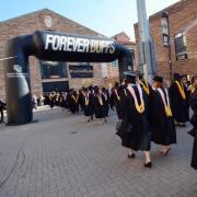 Graduates walk through Forever Buffs arch