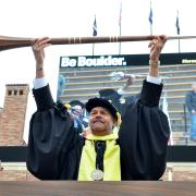 Jim Williams holds university mace, or staff, during 2017 commencement