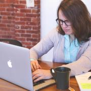 Woman looks at computer with confused look on face