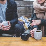 Two people having a conversation over coffee and tea