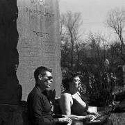 Two Archive Transformed residents sit against headstone