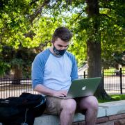 Student in mask works on laptop outside