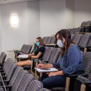 students physically distance in large lecture hall