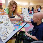 A CU engineering student helps a patient at the paper airplanes table during STEAM camp at Children's Hospital.