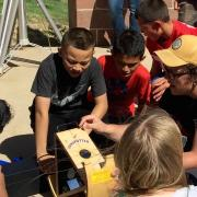 CU Boulder astronomy and physics student Sam Strabala searches for sunspots with middle schoolers in Keenesburg, Colorado as part of a science outreach program.