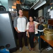 Students Adam Elbeck and Melina Dabney in Muenzinger Auditorium's projector room