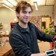 """Technology, Arts and Media student Kristof Klipfel poses with his """"piano glove"""""""