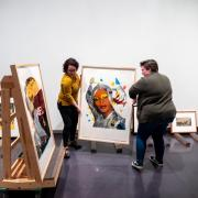 Students move artwork at the CU Art Museum's new exhibition, Persuasive Prints.