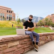 Student wearing mask working on laptop outside