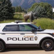 A CUPD car in front of a bronze buffalo statue on campus.