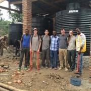 Curtis Gile and team in front of water catchment system