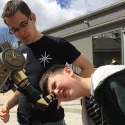 CU-STARs student volunteer helps child look through telescope