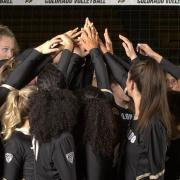 Colorado women's volleyball players stand in a huddle