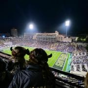 Football fans wearing Buffalo hats watch the game