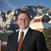 Dean David Ikenberry stands in front of the Leeds School of Business