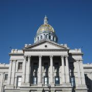 The tower of the state capitol building in Denver, Colorado, appears against a clear blue sky.