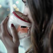 Person drinking hot chocolate out of a Santa mug