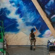 A mural being painted at CU Boulder's new aerospace building
