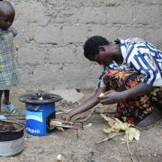 A family in Rwanda using a wood-burning cookstove as part of a large-scale delivery program