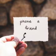 """Stock image of a person holding a note saying """"Phone a friend"""""""