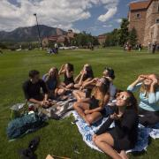 People sit on a campus lawn and take in the Great American Eclipse