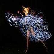 Emily Daub performs a modern dance while wearing LED-lit costume