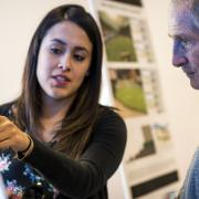 A student discusses a design drawing with a community member.