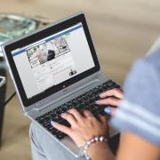 Woman checks Facebook on laptop computer