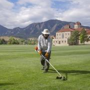 Facilities Management staff member uses trimmer on campus grounds