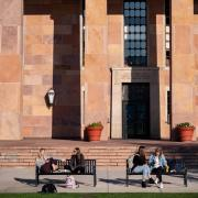 Students sitting on benches outside of Norlin Library