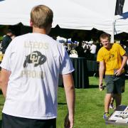 Students play corn hole on the lawn during a tailgate