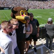 Family poses for photo with Chip at Family Weekend football game