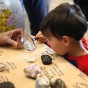 Child analyzes rocks under a magnifying glass
