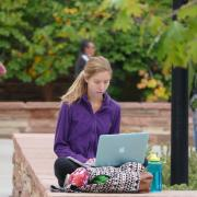 Student on laptop sitting outside on campus