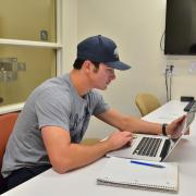 Student works on laptop computer at the Business Library