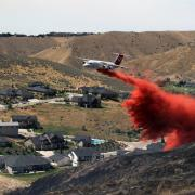 An airtanker drops retardant to help stop the spread of the 2015 Eyrie Fire in the foothills of Boise, Idaho, which was ignited by sparks from construction equipment.