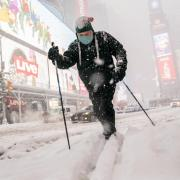 Person uses skis to traverse snowy New York City