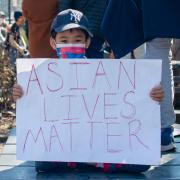 Asian American child in mask holding 'Asian Lives Matter' sign at a rally