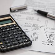 Calculator, budget sheet and pen