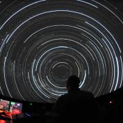 Person works controls at Fiske Planetarium's immersive theater
