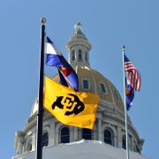 CU Boulder flag in front of Colorado capitol building.