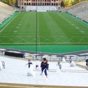 Students clean up Folsom Field after a game