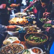 People serve themselves food buffet-style at a dinner party