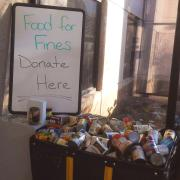 """""""Donate here"""" Food for Fines sign sits next to donated food items"""