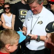 Coach Mike MacIntyre autographs a fan's hat