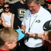 Coach Mike MacIntyre autographs a fan's hat